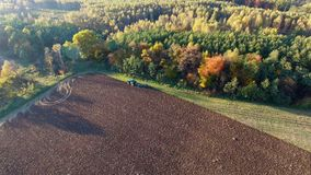 Aerial shot of tractor plowing black soil close to forest. Autumn sunset. stock video footage