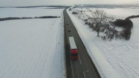 Aerial shot of truck and cars driving winter road in snowy field. Drone shoot stock video