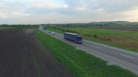 Aerial shot of truck driving a road benween fields. Sunset time. Spring season stock video footage