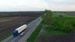 Aerial shot of truck driving a road benween fields. Sunset time. Spring season stock video