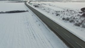 Aerial shot of truck driving winter road in snowy field. Drone shooting stock video footage