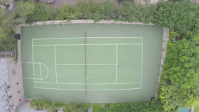 Aerial Shot of Two People Playing Tennis. Aerial shot of a private tennis court. Two people are enjoying a match below stock footage