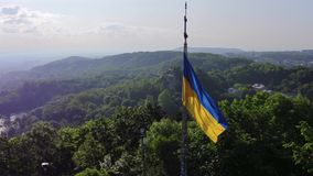 Aerial Shot Ukrainian National Flag Flying on Top of the Beautiful Panorama of the City Lviv. 4k. UHD stock video footage