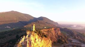 Aerial shot, Upezzinghi tower on the rocky outcrop in Italy, Tuscany, on the sunset light, filmed with drone, 4K stock footage