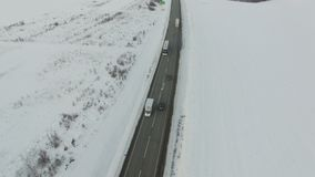 Aerial shot of vehicle and bus driving winter road in snowy field. Drone shooting stock footage