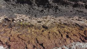 Aerial shot. Volcanic surface of the ocean coastline. Close-up of dark gray and yellow stones. Dolly shot from the. Turquoise color of the ocean waves stock video footage