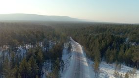 Aerial shot of winter road in conifer forest on background of winter landscape stock footage