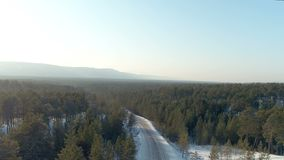 Aerial shot of winter road with lonely approaching car. Background snowy north forest. Landscape stock footage
