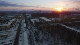 Aerial view of cargo train crossing winter city at sunrise. St. Petersburg. Aerial shot of winter St. Petersburg and freight train running through city at dawn stock video