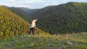Aerial shot of a young couple standing on top of a mountain on enjoy a beautiful view of the valley. A woman hugs her stock video footage