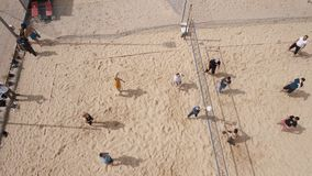 Aerial shot young people playing volleyball at beach sports ground, sunny day stock footage