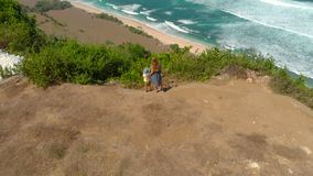 Aerial shot of a young woman and her son visiting a remote beach - nyang nyang- on the Bali island. Standing on a rock. Looking at an open ocean in front of stock video
