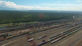 Aerial shots are moving along the railway junction. Showing trains parked next to each other with multi-colored roofs and colorful sides of the train between stock footage