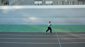 Drone shot of overweight runner during training. Aerial side view of plus size female in sportswear jogging at stadium on sunny morning. Active fat woman runner stock video