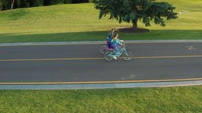 Drone shot of lesbian couple biking outdoors. Aerial side view of same-sex couple in love riding bicycles on bike path in countryside park. Young women with lgbt stock footage