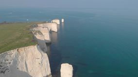 An aerial sideway Left to right footage of the Old Harry Rocks with crystal blue water along beautiful white cliffs under an ama stock video