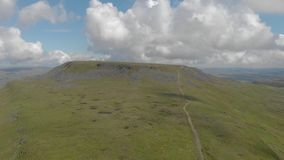 An aerial sideway left to right footage of a rocky summit mountain with green slope and trail path under a majestic blue sky stock footage