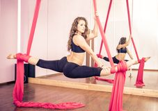Aerial silk athlete. Beautiful dancer training with aerial silk in a fitness studio stock photography