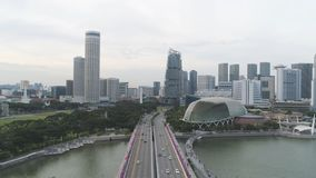 Singapore - 25 September 2018: Aerial for Singapore with many cars on the bridge above the lake and city buildings stock images