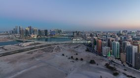 Aerial skyline of Abu Dhabi city centre from above day to night timelapse. Aerial skyline of Abu Dhabi city centre from above day to night transition timelapse stock footage