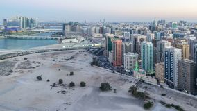 Aerial skyline of Abu Dhabi city centre from above day to night timelapse. Aerial skyline of Abu Dhabi city centre from above day to night transition timelapse stock video footage