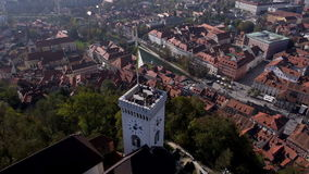 AERIAL, slow mo: People on a tower of the Ljubljana Castle. Cityscape in the background stock footage