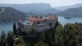 AERIAL, slow motion: Bled Castle with lake island in the background stock video