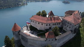 AERIAL, slow motion: Majestic Bled Castle above the lake stock footage