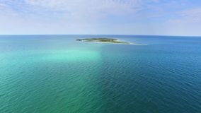AERIAL: Small island in shallow waters of blue sea. Flying above shallow waters towards small island in blue sea, aerial view, drone point of view stock video footage
