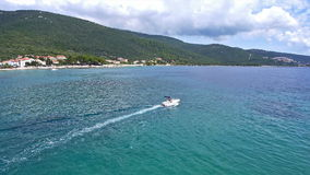 Aerial: small speedboat driving to an open sea, leaving the marina stock video footage
