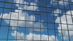 AERIAL. Smooth camera movement in front of office building windows reflecting sunny blue sky with white puffy clouds. 4k stock footage