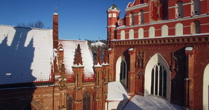 AERIAL. Smooth flight through Church of St. Anne`s Onos towers covered by snow, Vilnius, Lithuania. Sunny winter day. 4k. AERIAL. Flight through Church of St stock video footage