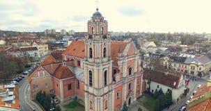 AERIAL. Smooth flight up beautiful Church of All Saints (Visu Sventuju) in Vilnius old town, Lithuania. Panorama of Vilnius stock footage