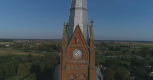 Aerial. Smooth tilt / crane drone shot of St. John church of Ramygala in Lithuania. Panorama of city in early autumn. 4k stock video footage