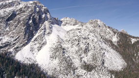 AERIAL: Snowy mountain walls with spruce forest beneath stock video