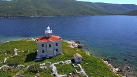 Aerial: solitude lighthouse on a small island with crystal clear blue water stock video