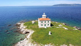 Aerial: solitude lighthouse on a small island with green field and turquoise sea stock video footage