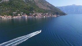 Aerial speedboat near the town of Perast. A fast moving boat goes to the city of Perast along the Adriatic Sea. Montenegro stock footage