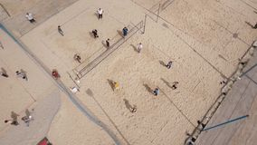 Aerial spinning shot people playing volleyball at beach playground, sunny day stock footage
