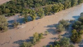 Aerial spring river flood in forest. Top aerial view of muddy flood river flow in forest stock video