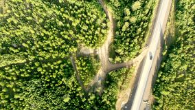 Aerial stable shot over a country road with few cars driving between forests on a sunny day.