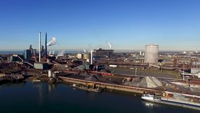 Aerial of a steel factory. Drone footage of a steel factory near the ocean stock video footage