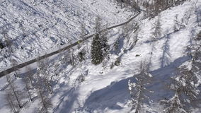 AERIAL: Steep mountain terrain with spruce trees. Car driving on a plowed road stock footage