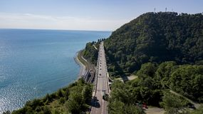 Aerial stock photo of car driving along the winding mountain pass road through the forest in Sochi, Russia royalty free stock images