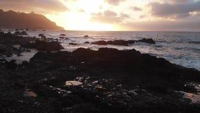 aerial Strand bei Sonnenuntergang Die Ansicht öffnet sich, um Steine und vulkanischen Sand, die goldene Stunde zu schwärzen die K stock video footage