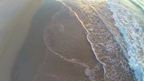 Aerial of sunrise tide rolling onto beach. Video of aerial of sunrise tide rolling onto beach stock footage