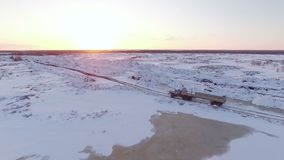 Aerial sunset view of heavy truck driving on snow-covered winter road.  stock footage
