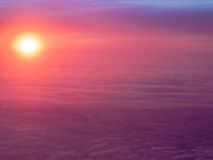 Aerial Sunset View. The sun setting into the cloud layer over England, viewed from an aeroplane cabin window royalty free stock images