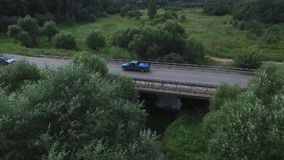 Aerial survey of the car rides on the serpentine. Flying over red cabriolet drive the street.Aerial view of red car. Which goes over the bridge. Traffic on the stock video footage