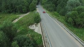 Aerial survey of the car rides on the serpentine. Flying over red cabriolet drive the street.Aerial view of red car. Which goes over the bridge. Traffic on the stock video